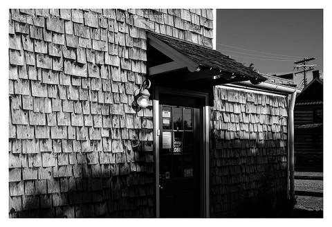 BW photograph of a shingled store.