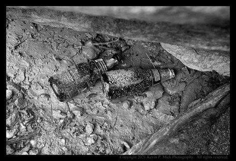 BW photograph of two beer bottles under some rocks and splattered with mud.