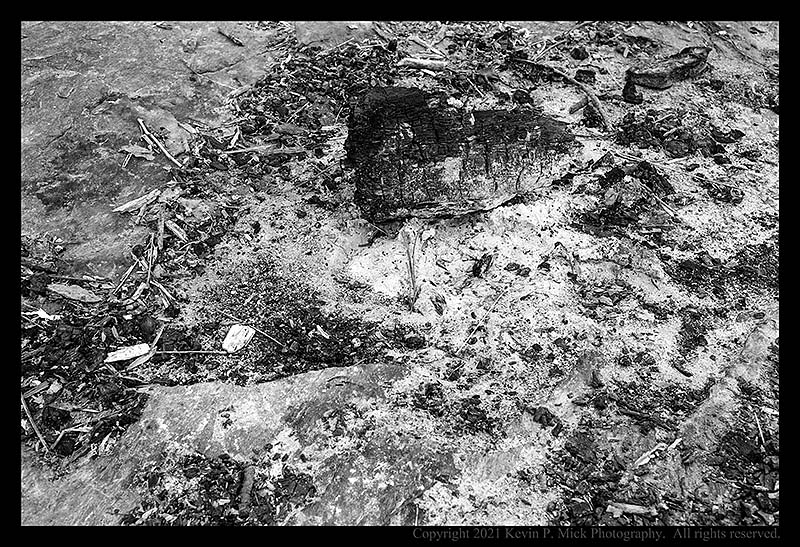 BW photograph of the remains of a fire (log and ashes) laying atop a large boulder.