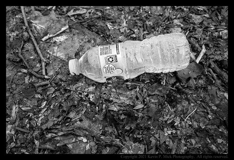 BW photograph of a full water bottle laying on the ground amid some leaves.