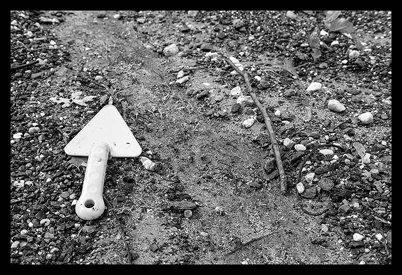 BW photograph of a plastic spade near some run-off after a thunderstorm.