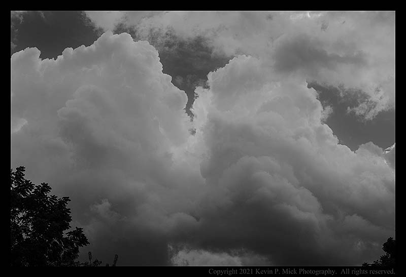 BW photograph of cumulus clouds morphing into a storm.