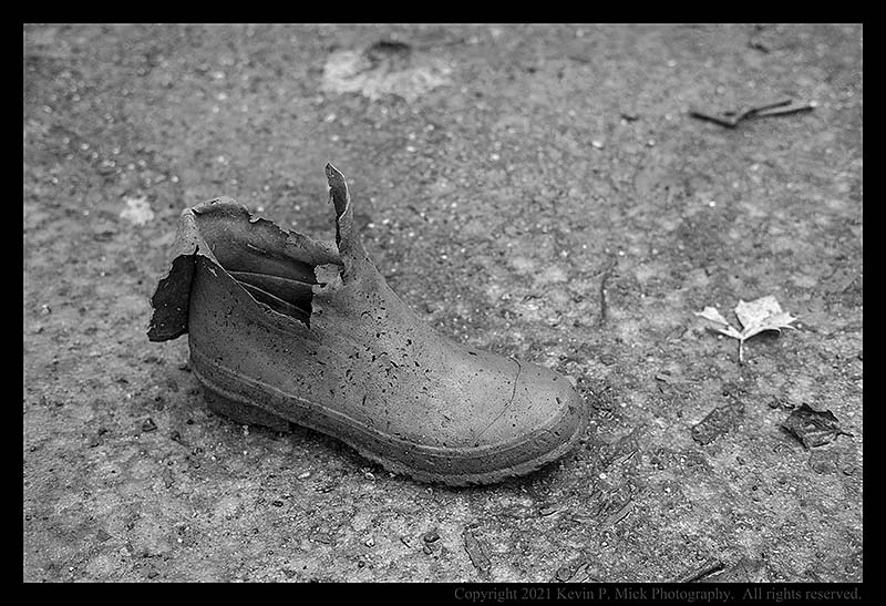 BW photograph of a damaged waterboot sitting in a mudflat.
