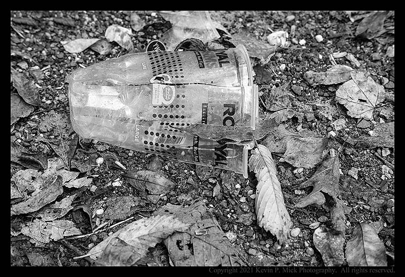 BW photograph of a shredded plastic cup in a parking lot.