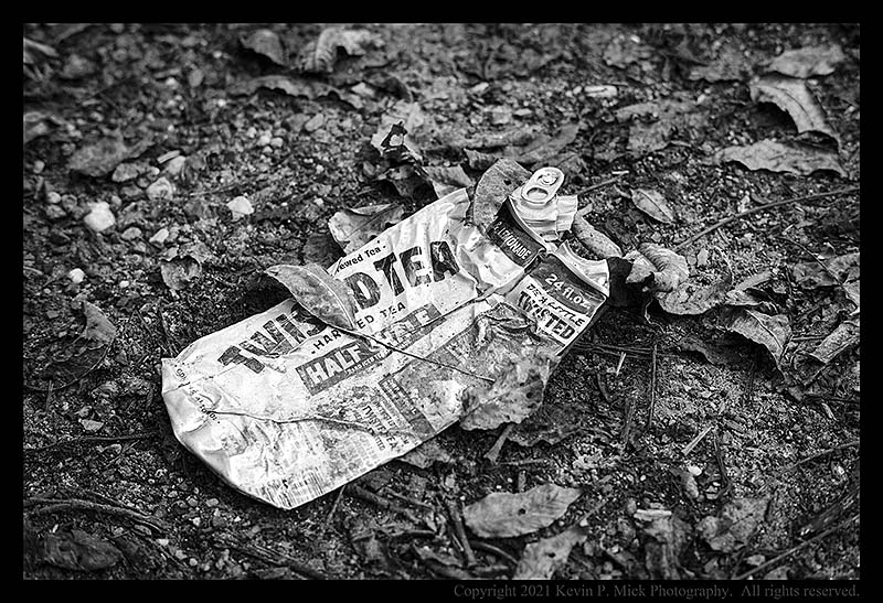 BW photograph of an aluminum can crushed and left behind.