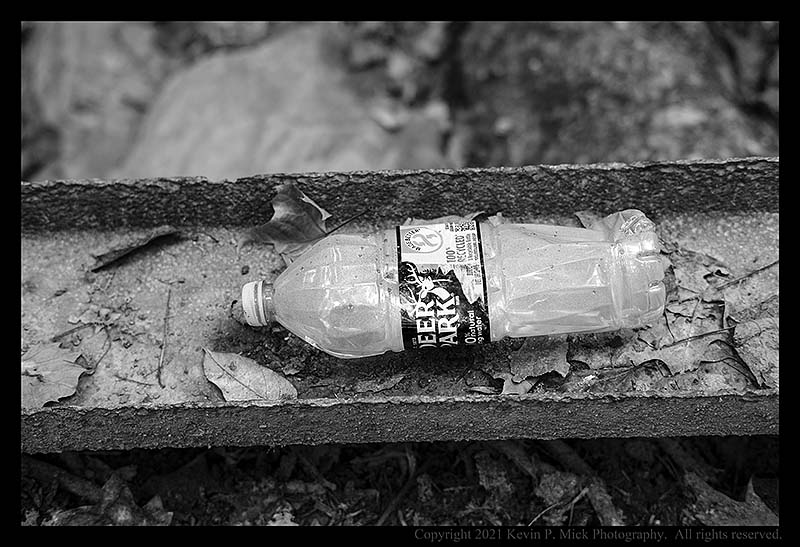 BW photograph of a filled plastic water bottle left behind.
